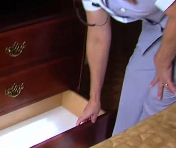 Limpiadora del hotel abre cómoda en la habitación de la pareja mayor